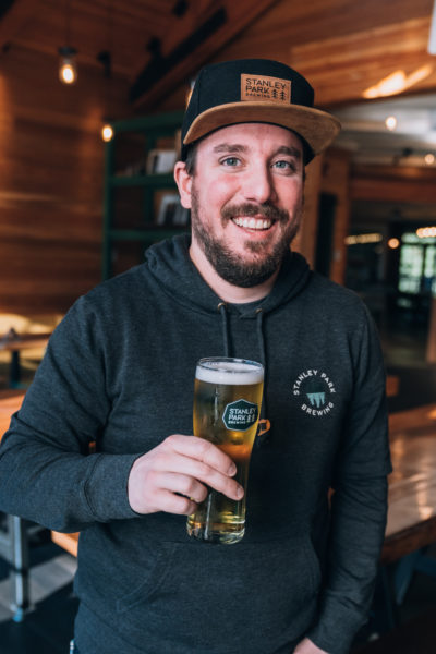 Brewer holding a stanley park brewing beer