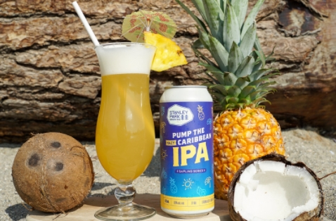 a can of pump the caribbean hazy ipa by stanley park brewing surrounded by tropical fruit on a beach with the beer in a piña colada glass